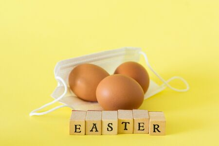 Word easter written with wooden letters on yellow background, concept photography