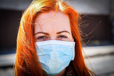 Beautiful young European woman with ginger coloured hair on the street with a medical face mask on