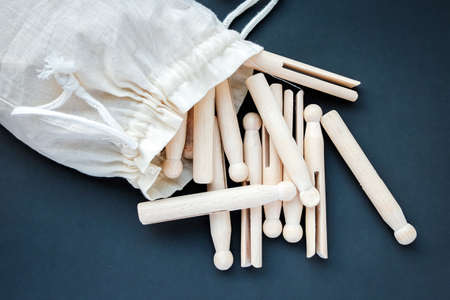 Wooden vintage retro clothes pegs in a white cloth bag