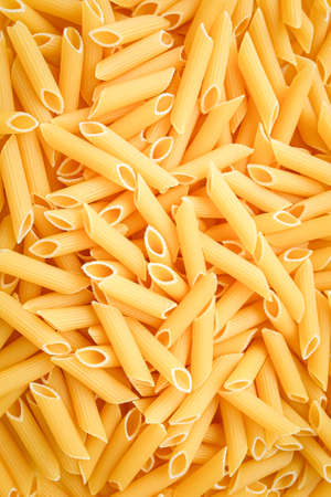 Uncooked penne pasta close up, background. Vertical photo