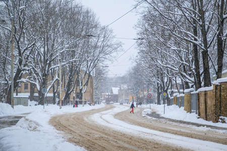 Snowstorm and snow-covered street and cars with a lonely pedestrian Standard-Bild - 163387850