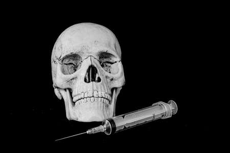 Death from the vaccine concept - human skull model and syringe. Banco de Imagens