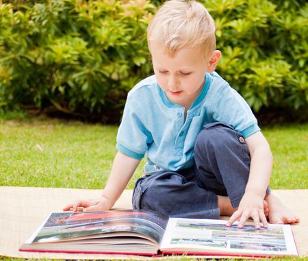 Sitzen Junge liest ein Buch im Garten