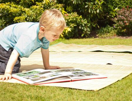 Junge liest ein Buch auf einer Matte im Garten