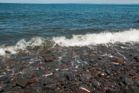 Welle Waschen über Kiesstrand