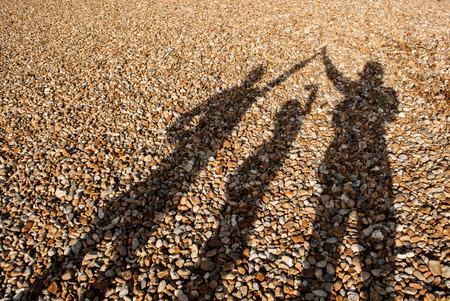 Full-Frame von Kieselstrand mit Schatten von 3 Personen Standard-Bild