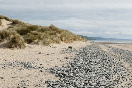low down shot of beach with pebbles and grassy dunes in Ynyslas, Wales, UK Standard-Bild