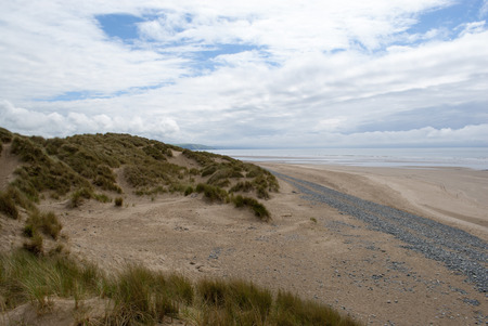 low down shot of beach with pebbles, grassy dunes and contrasting sky in Ynyslas, Wales, UK