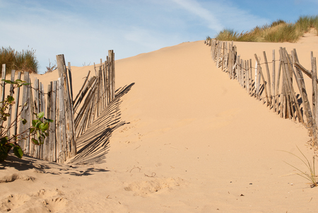 seascape image of broken fence creating a path through sand Stock Photo