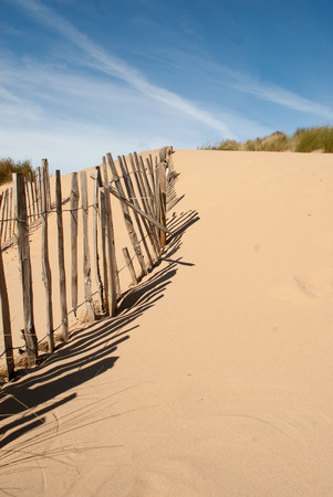 seascape image of a broken old fence leading up a sand dune