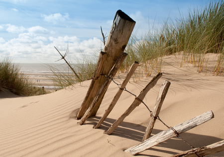 seascape view of a broken old fence remnants on a sand dune with sea in the background