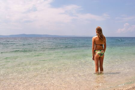 Young Caucasian female in bikini standing in shallow sea facing the horizon