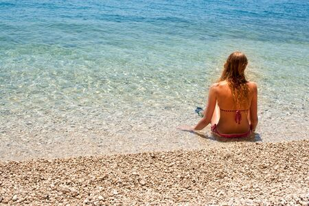 Young blond female sitting at the edge of a calm shallow blue sea, looking to the right