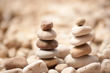 Horizontal image of two small zen pagodas to the right hand side of five pebbles against a blurred background of pebble beach