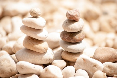 Horizontal image of two small zen pagodas of five pebbles against a blurred background of sea and pebble beach