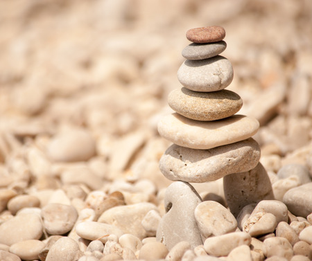 Zen tower of six stones stacked on stilts on a pale pebble beach, square image Standard-Bild