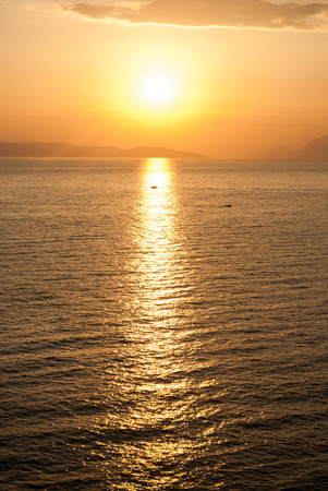 golden sunset over the sea with sun high in the sky and a boat in the beam of light Standard-Bild