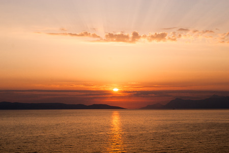 horizontal image of golden sunset with sun centrally low above the sea and sunrays coming through clouds above