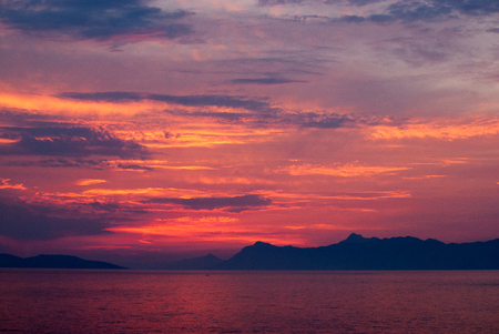 Horizontal image of deep coloured sunset with sea in red, golden and purple colours, black mountains on the horizon,