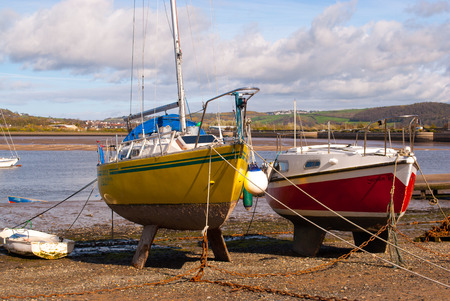 Two small fishing boat on sand at low tide in Conwy, Wales Editorial