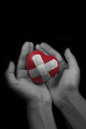 herida: Foto de las manos sosteniendo un coraz�n herido. Foto de archivo