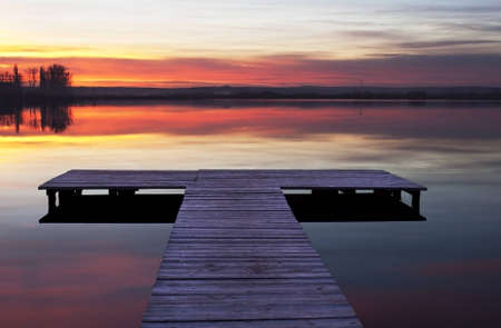 Photography of a lake and a jetty at the sunset