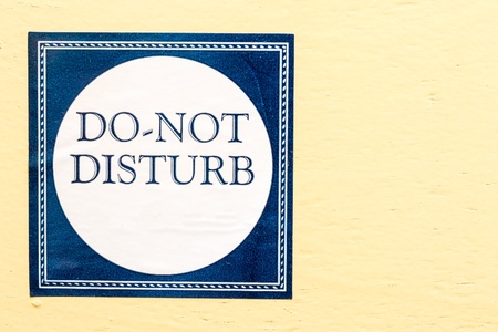 unwelcome: Do not disturb sticker on a wall