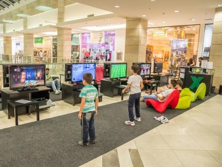 niños jugando videojuegos: Niños jugando a videojuegos en centro comercial AFI Cotroceni, Bucarest Editorial