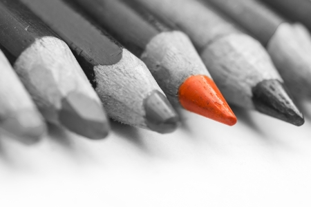 standing out from the crowd: Closeup Of An Orange Crayon Standing Out Of A Larger Bunch Of Crayons Stock Photo