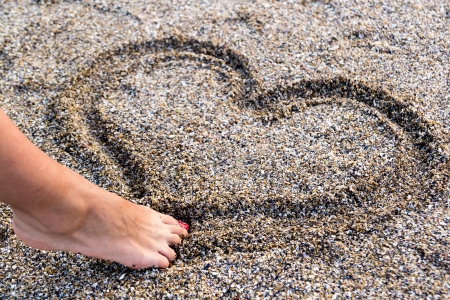 love confession: Young Girl Drawing A Heart In The Sand With Her Foot
