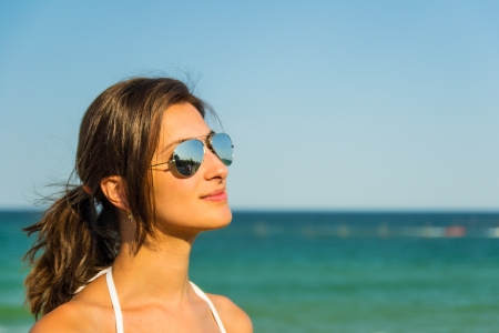 Beautiful Girl With Sunglasses And Swimsuit Looking In The Sky With The Sea As Background photo