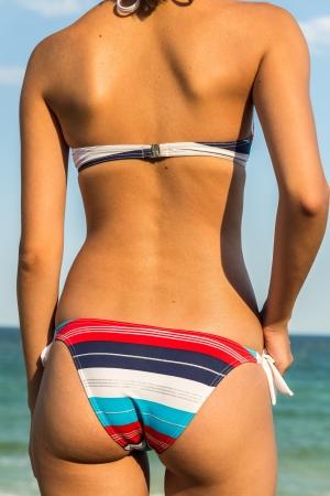 belles jambes: Jeune Fille Sexy Avec un beau bronzage posant dans son maillot de bain Against The Ocean