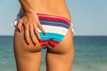 Closeup foto di una ragazza sexy in bikini afferrandola inferiore su una spiaggia Archivio Fotografico - 18664866