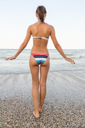 Beautiful Sexy Girl On The Beach Walking Toward The Water photo