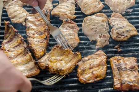 Closeup Of Man Preparing Pork Stakes On Barbecue photo