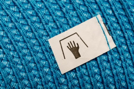 Manual Wash Label On A Blue Cloth Stock Photo - 18762635