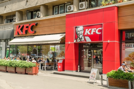 specializes: BUCHAREST, ROMANIA - MAY 15: People Eating At Kentucky Fried Chicken Restaurant on May 15, 2013 In Bucharest, Romania. It is a fast food restaurant which specializes in fried chicken.