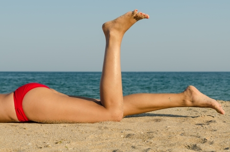 hot girl lying: Feet Closeup Of Young Girl On Holiday Relaxing On Beach On A Sunny Day Stock Photo