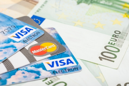 credit union: BUCHAREST, ROMANIA - DECEMBER 22, 2013  Visa And Mastercard Credit Cards Over European Union Official Euro Banknotes Editorial