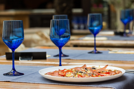 Empty Blue Glasses And Fresh Served Pizza On Restaurant Table