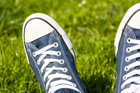 Retro Sneakers On Green Grass Background photo