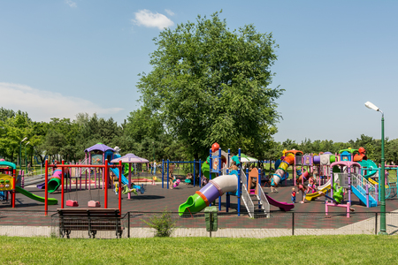 BUCHAREST, ROMANIA - JUNE 08, 2014  Happy Children Having Fun In Youths Public Park  Tineretului Park  Playground On Summer Day  Created in 1965 is one of the largest fun parks in south Bucharest
