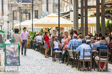BUCHAREST, ROMANIA - JULY 04, 2014  Tourists Having Lunch At Outdoor Restaurant Downtown Lipscani Street  Lipscani is one of the most busiest streets of central Bucharest  Editorial