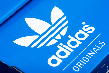 adidas: BUCHAREST, ROMANIA - JULY 23, 2014  Adidas Sign On Adidas Shoe Box  Founded in 1924 is a German multinational corporation that designs and manufactures sports shoes, clothing and accessories