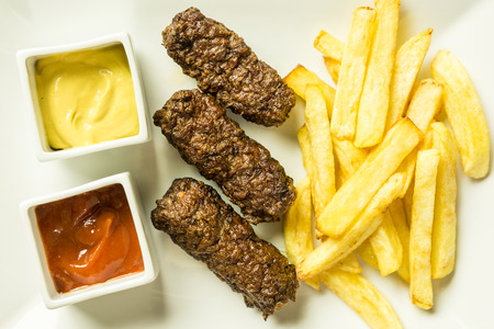 Traditional Romanian Mici And French Fries With Ketchup And Mustard Close Up photo
