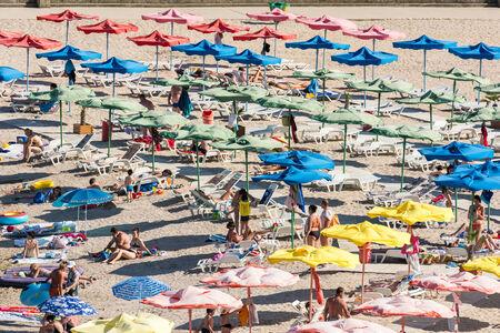 hot summer: OLIMP, Rumania - 31 de julio 2014: Multitud de personas se relaja bajo parasoles de playa en d�a de verano caliente. Editorial