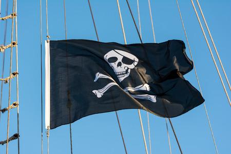 Black Pirate Flag With Human Skull On Blue Sky Stockfoto