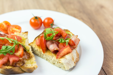 Fresh Bruschetta Sandwich With Bacon, Rucola And Tomatoes photo