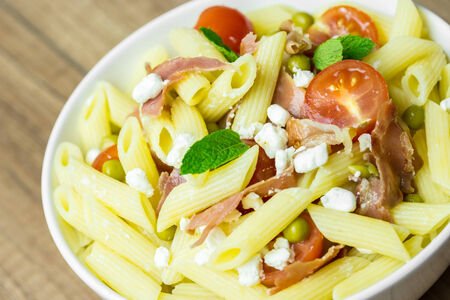 Italian Penne Pasta Salad With Mozzarella, Tomatoes And Prosciutto Ham photo