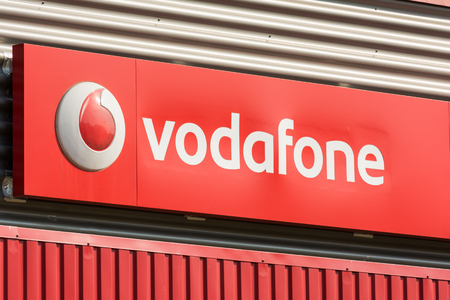 headquartered: BUCHAREST, ROMANIA - AUGUST 06, 2014: Vodafone Store Sign. It is the worlds second-largest mobile telecommunications company headquartered in London. Editorial